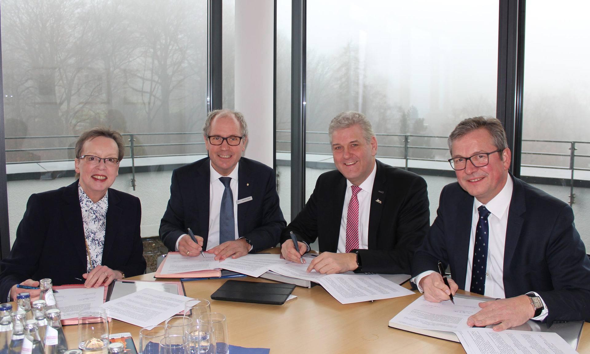 Regierungspräsidentin Marianne Thomann-Stahl, Landrat Manfred Müller, Bürgermeister Werner Peitz und Bürgermeister Michael Dreier beim Unterzeichnen des Kooperationsvertrag zur Digitalen Modellregion OWL.