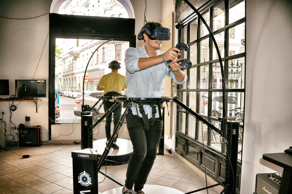 """Zwei männliche Personen mit VR-Brille testen den Virtualizer. Der """"Virtualizer"""" – ein omnidirektionales Laufband – ermöglicht es, den Körper auf eine sehr realistische Weise durch virtuelle Welten laufen zu lassen. Die Steuerung funktioniert dabei nur durch die eigene Körperbewegung."""