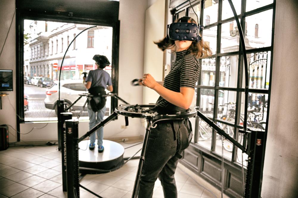 """Zwei weibliche Personen mit VR-Brille testen den Virtualizer. Der """"Virtualizer"""" – ein omnidirektionales Laufband – ermöglicht es, den Körper auf eine sehr realistische Weise durch virtuelle Welten laufen zu lassen. Die Steuerung funktioniert dabei nur durch die eigene Körperbewegung."""